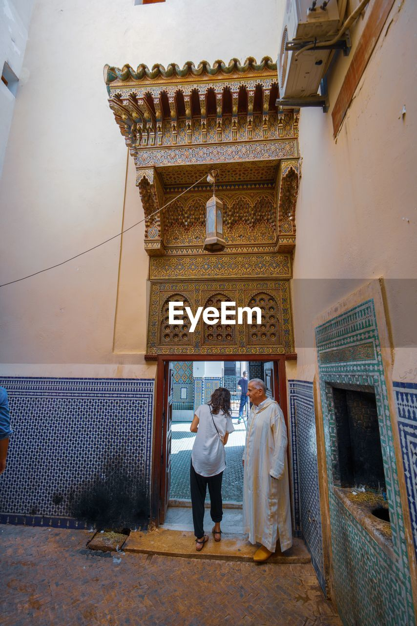 architecture, real people, built structure, one person, full length, rear view, building, building exterior, entrance, women, lifestyles, adult, door, religion, day, place of worship, standing, spirituality, belief