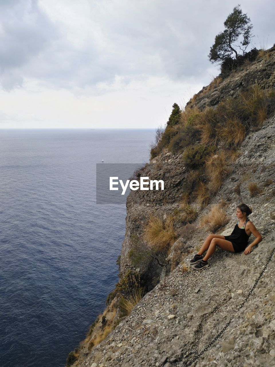 Young woman sitting on mountain by sea against sky