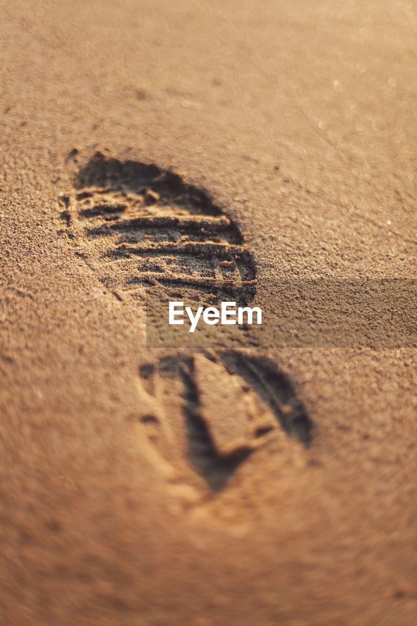 Close-Up Of Footprint On Sand At Beach