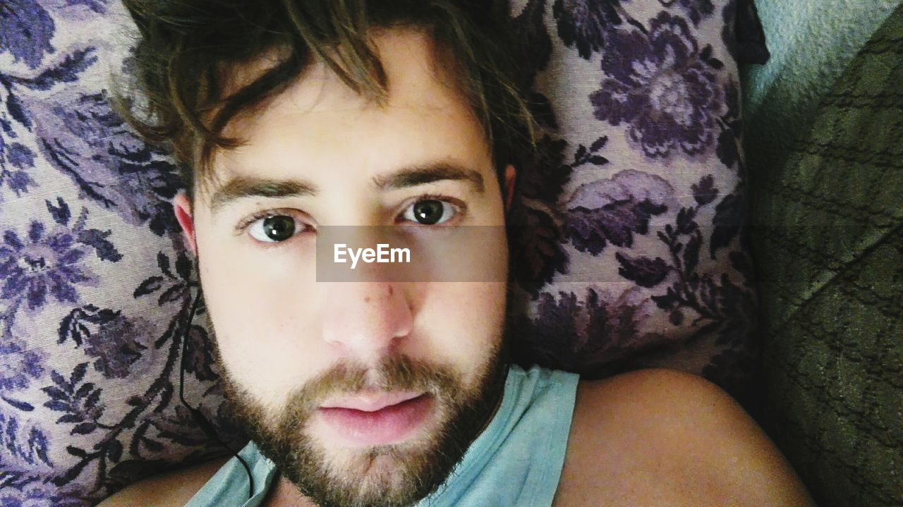 Close-up portrait of man listening music while lying on bed