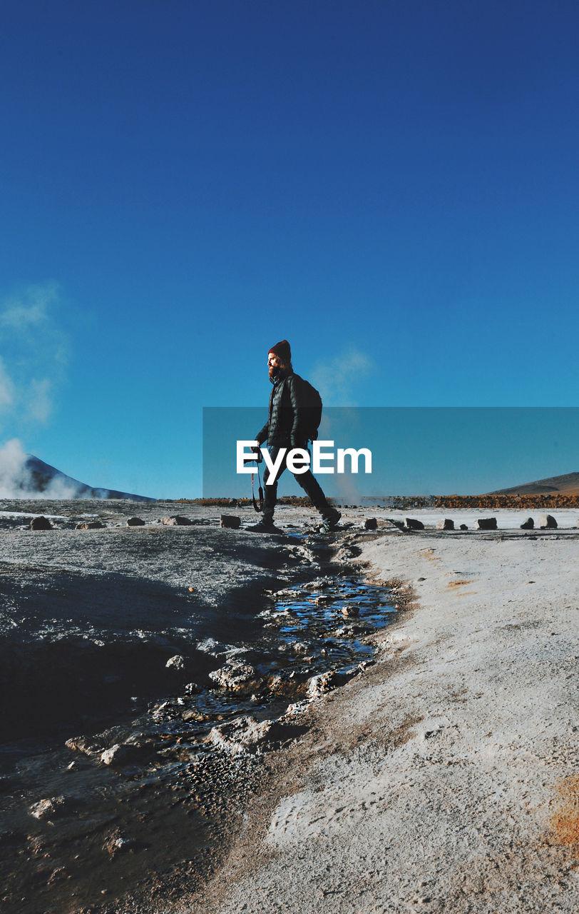 MAN WALKING ON ARID LANDSCAPE