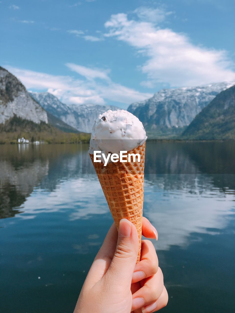 Close-Up Of Hand Holding Ice Cream Against Lake