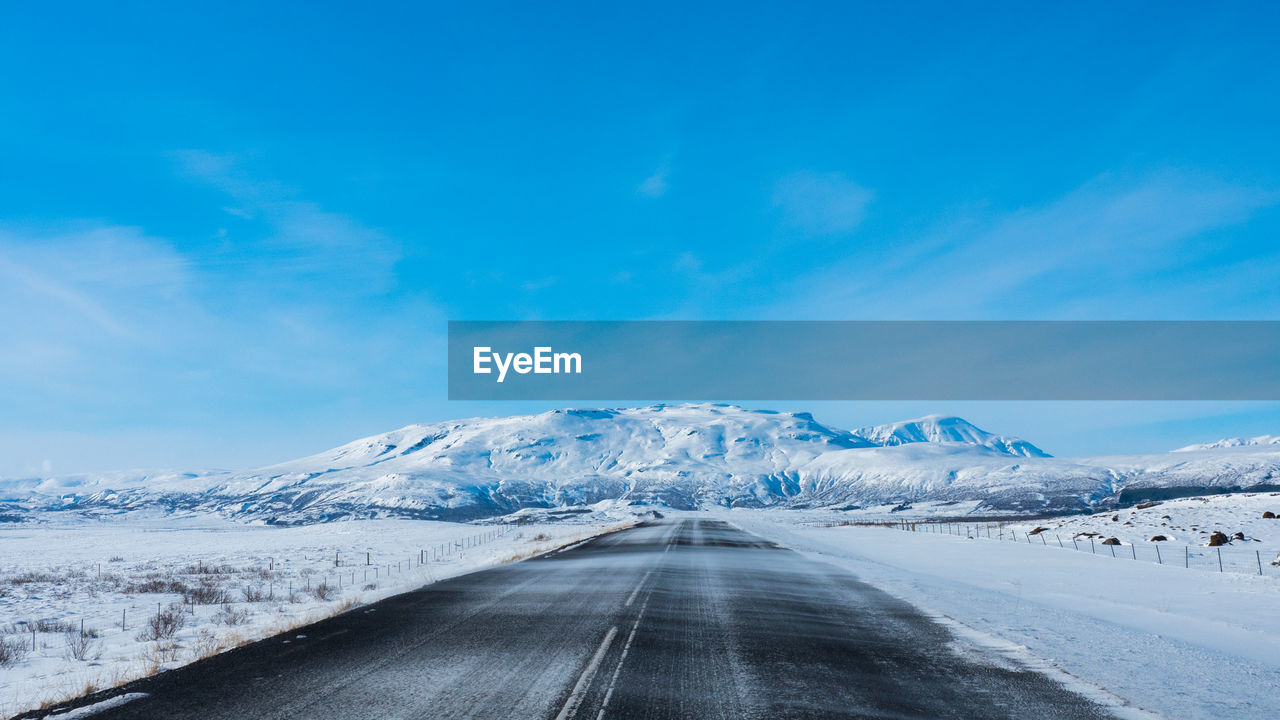 snow, cold temperature, sky, winter, road, cloud - sky, beauty in nature, scenics - nature, direction, mountain, the way forward, transportation, tranquil scene, nature, day, tranquility, no people, landscape, diminishing perspective, snowcapped mountain