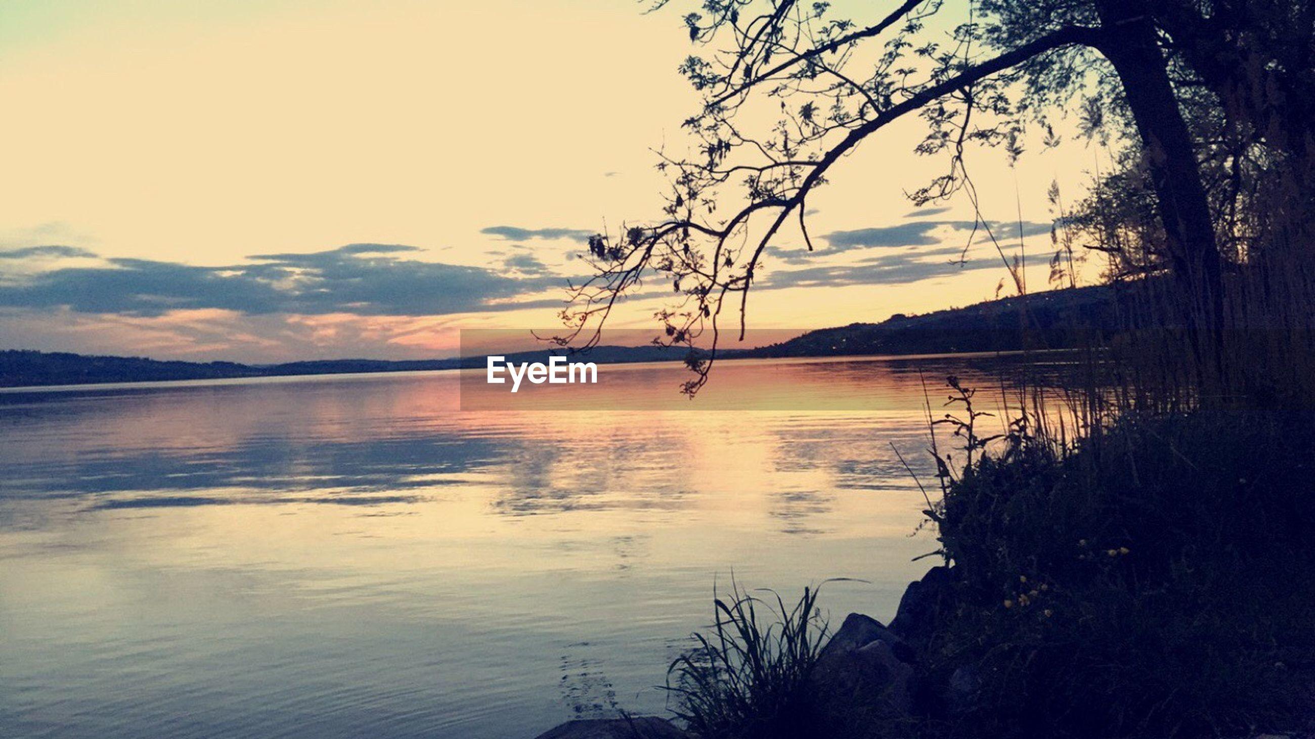 water, sunset, tranquil scene, tranquility, scenics, silhouette, beauty in nature, sky, reflection, lake, mountain, tree, nature, idyllic, sun, sea, nautical vessel, cloud - sky, non-urban scene, mountain range