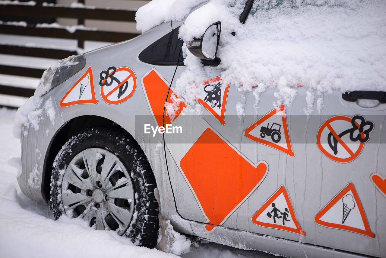 mode of transportation, snow, transportation, winter, cold temperature, white color, motor vehicle, car, land vehicle, no people, day, blizzard, wheel, tire, orange color, outdoors, nature, snowing, communication