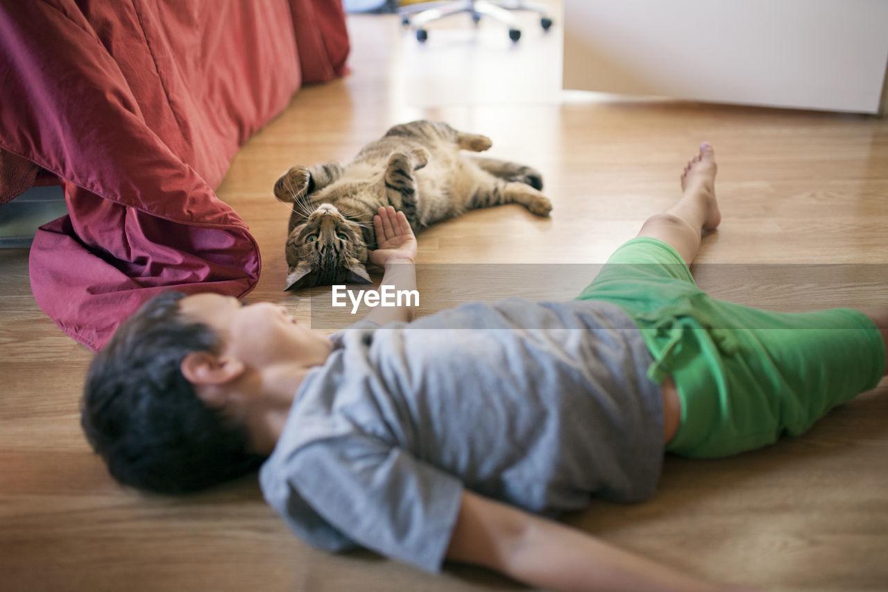 WOMAN LYING DOWN ON WOODEN FLOOR