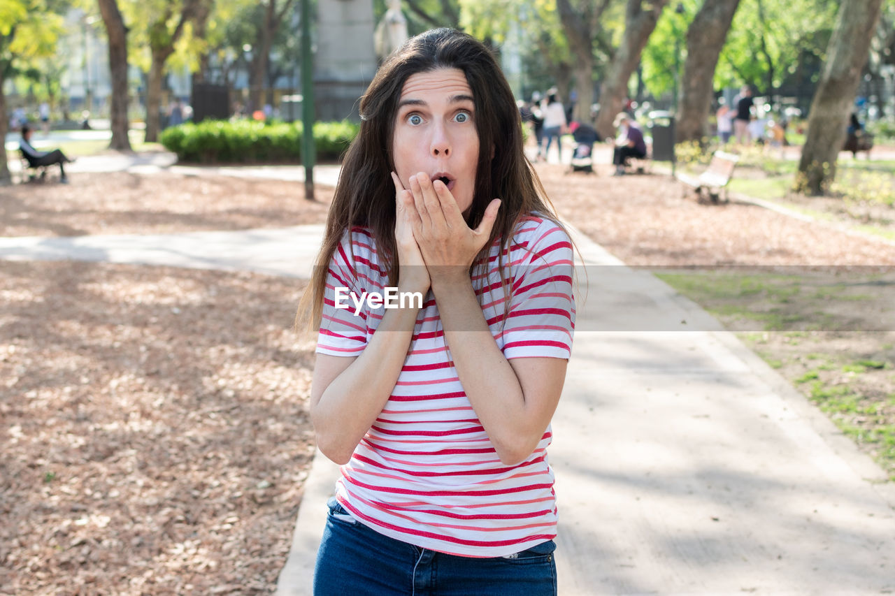 Portrait of woman making face while standing at park