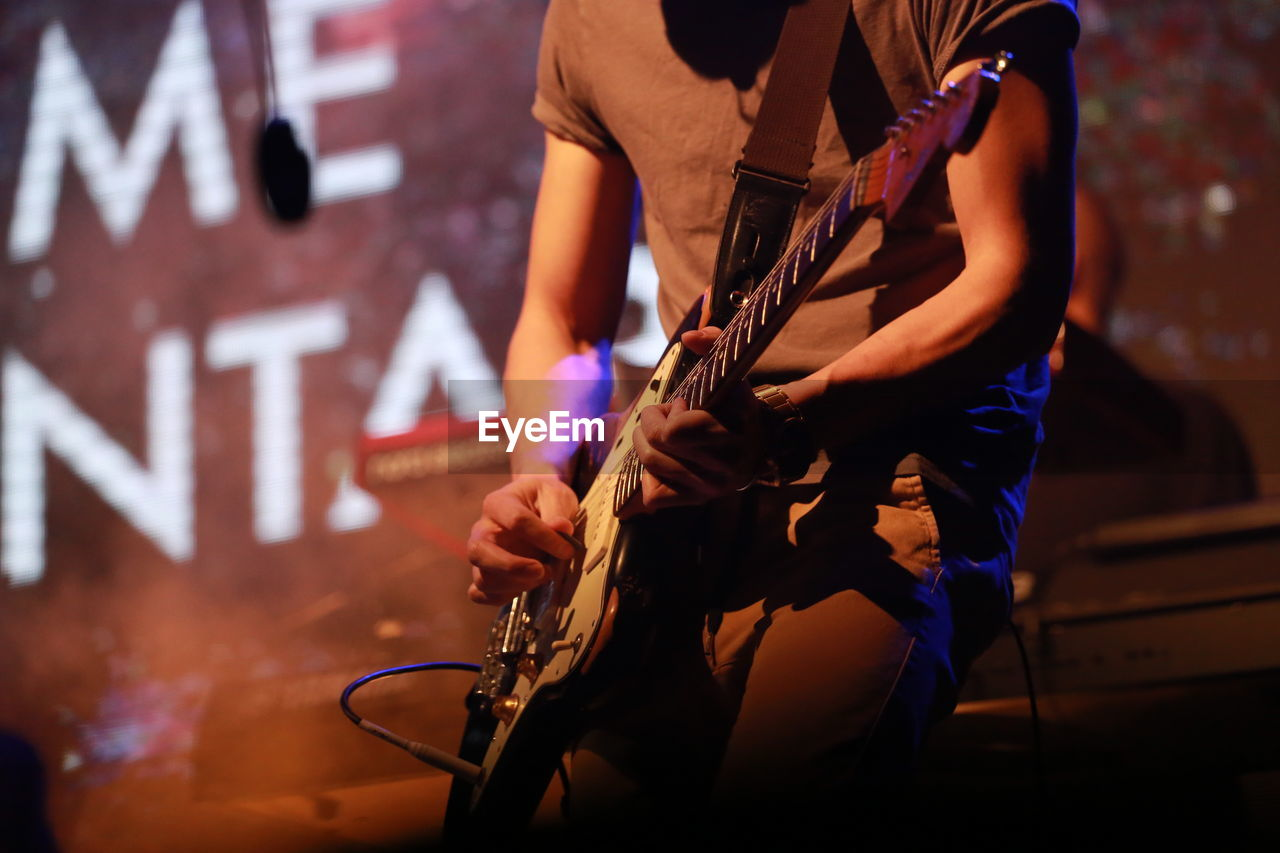 Midsection Guitarist Performing On Stage At Music Concert