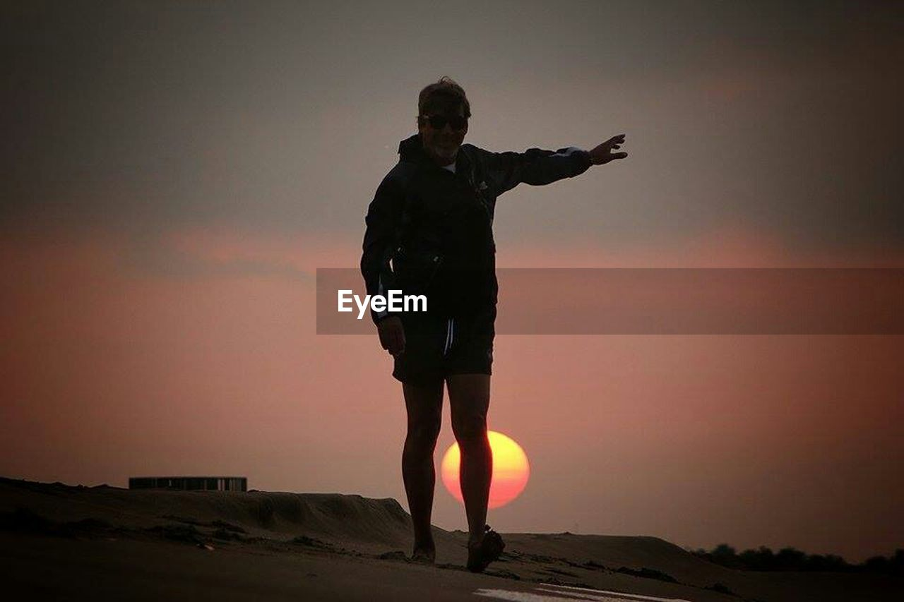 sunset, limb, standing, full length, silhouette, sky, one person, human arm, adults only, adult, outdoors, rock - object, nature, people, desert, one man only, landscape, night, beauty in nature, only men, young adult, horizon over water, human body part