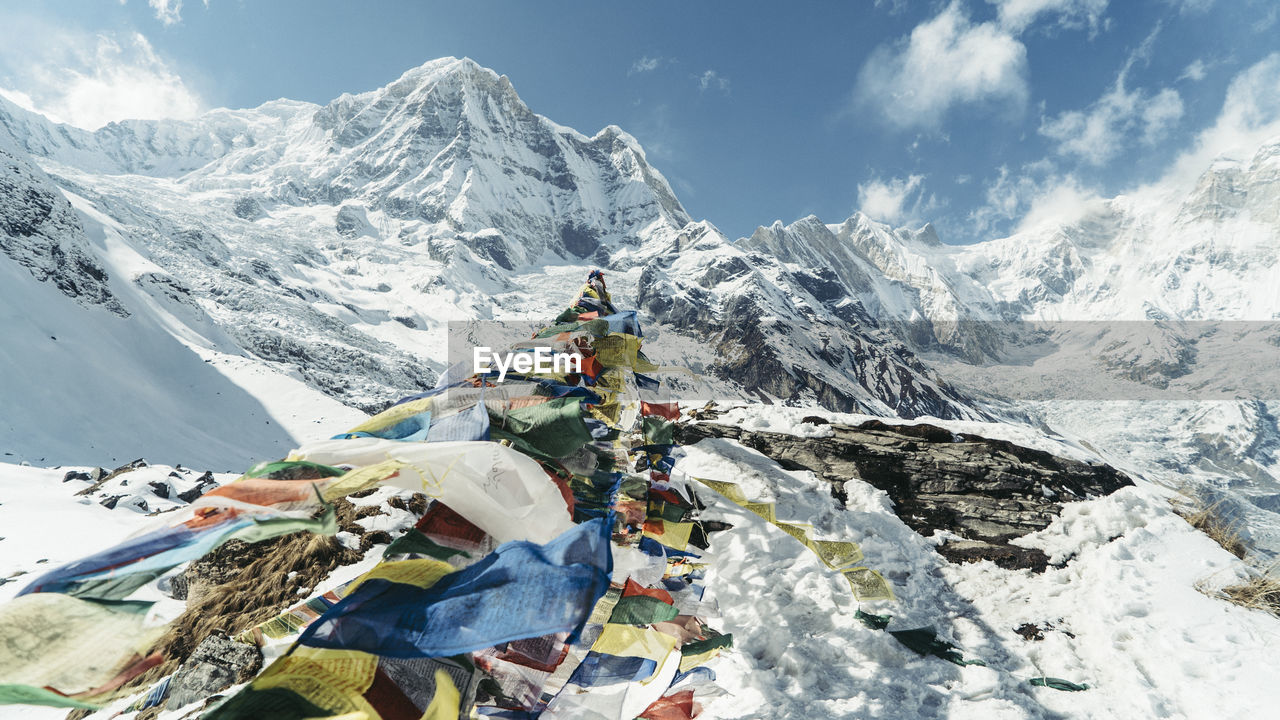 Prayer flags on machapuchare snowcapped mountains against sky