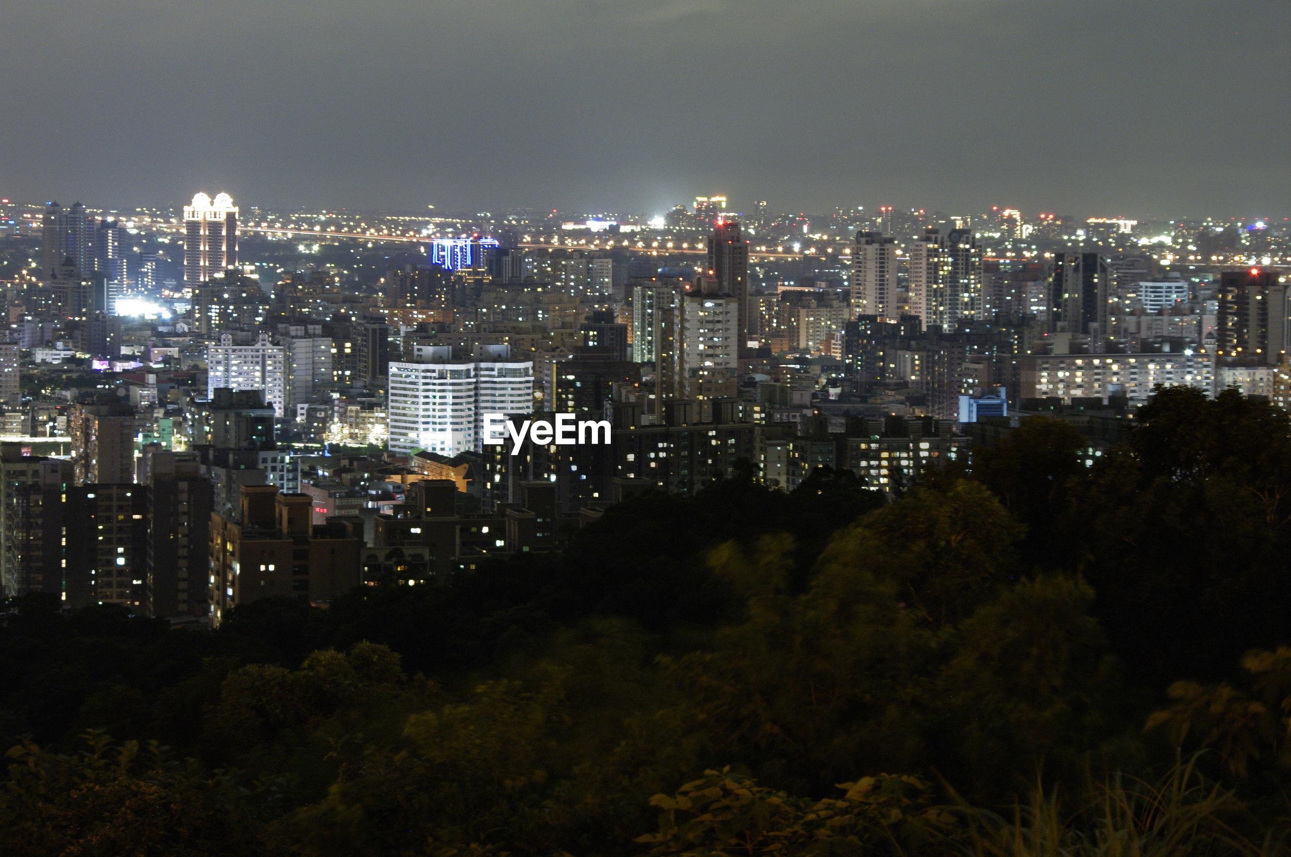 ILLUMINATED CITY BUILDINGS AGAINST SKY AT NIGHT