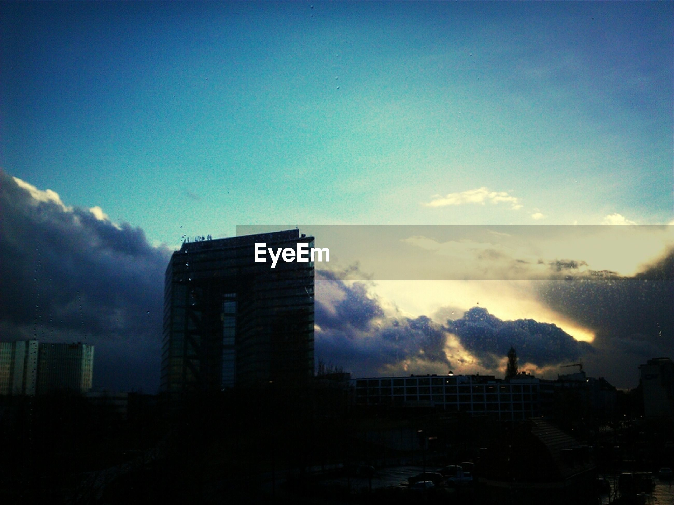 building exterior, architecture, built structure, sky, city, sunset, cloud - sky, cityscape, silhouette, cloud, building, residential building, dusk, cloudy, low angle view, outdoors, skyscraper, city life, residential structure, no people