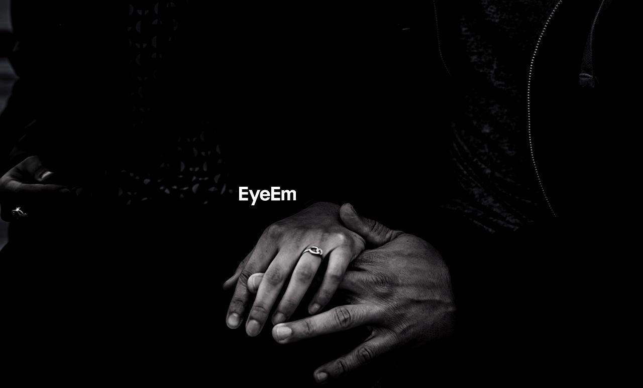 Cropped Hands Of People In Darkroom