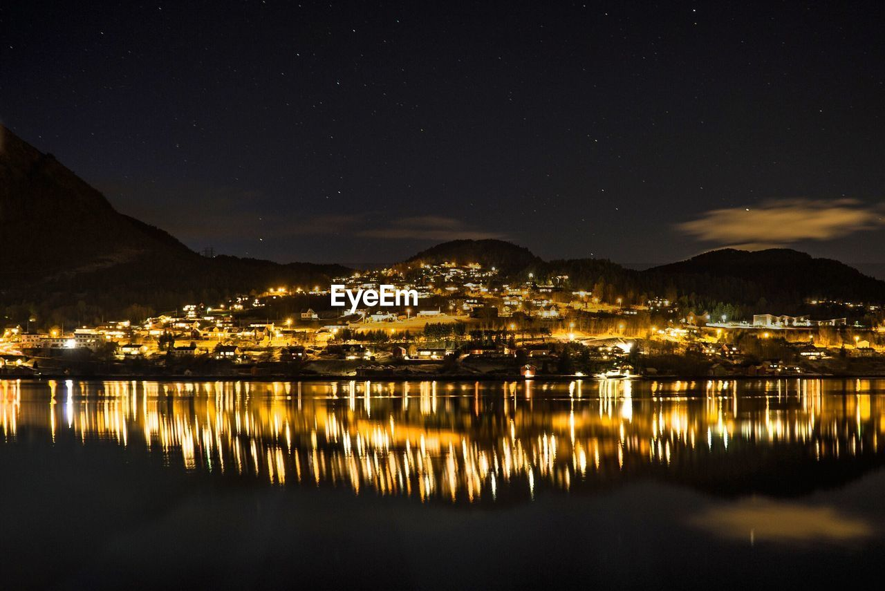 SCENIC VIEW OF LAKE BY ILLUMINATED CITY AGAINST SKY