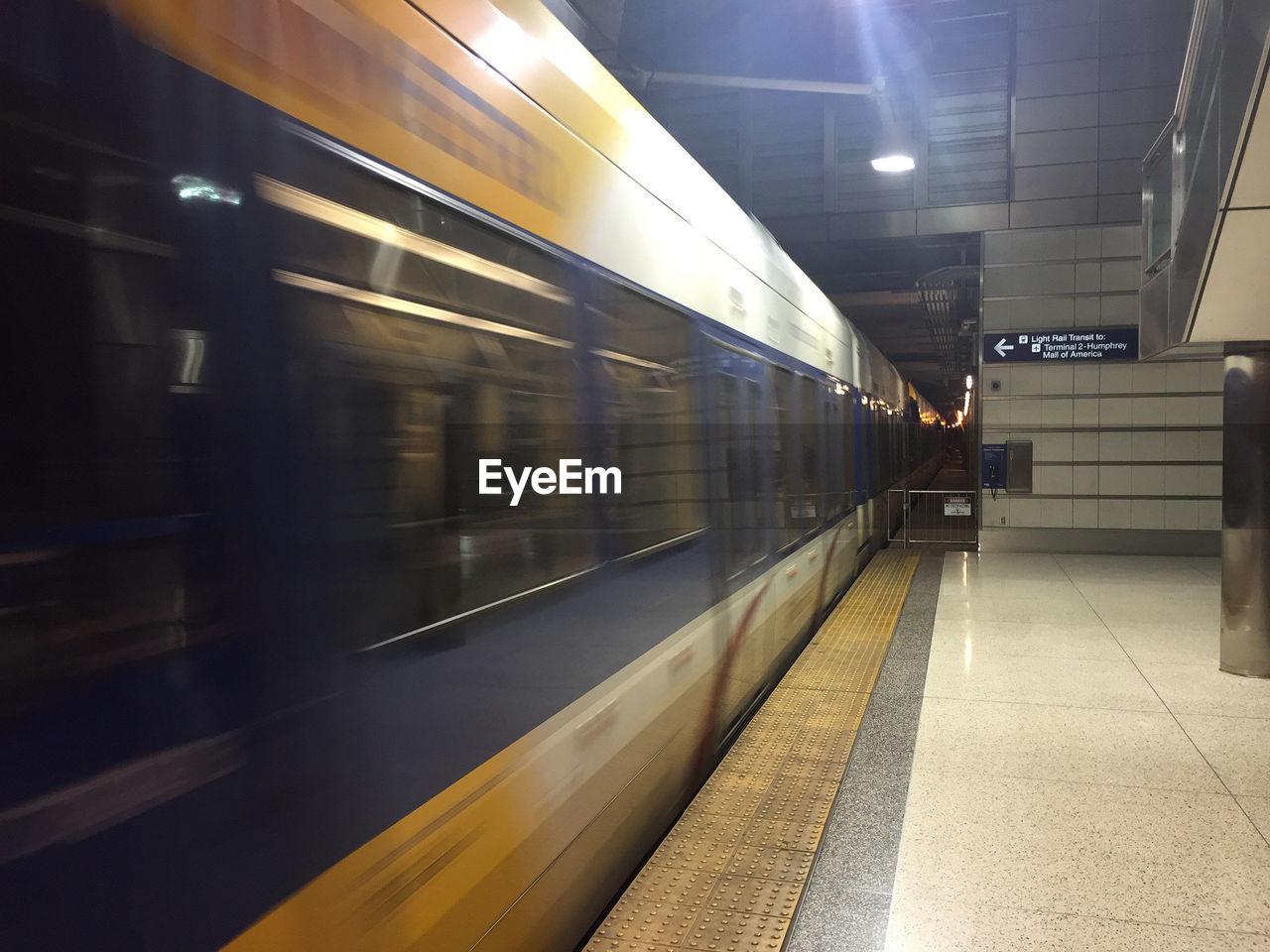 transportation, illuminated, rail transportation, train - vehicle, public transportation, railroad station platform, railroad station, blurred motion, indoors, mode of transport, motion, night, no people
