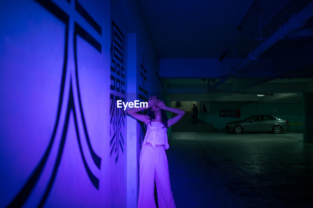 illuminated, blue, transportation, motor vehicle, indoors, mode of transportation, car, real people, land vehicle, night, architecture, wall - building feature, people, standing, purple, nightclub, representation, rear view, nightlife, luxury