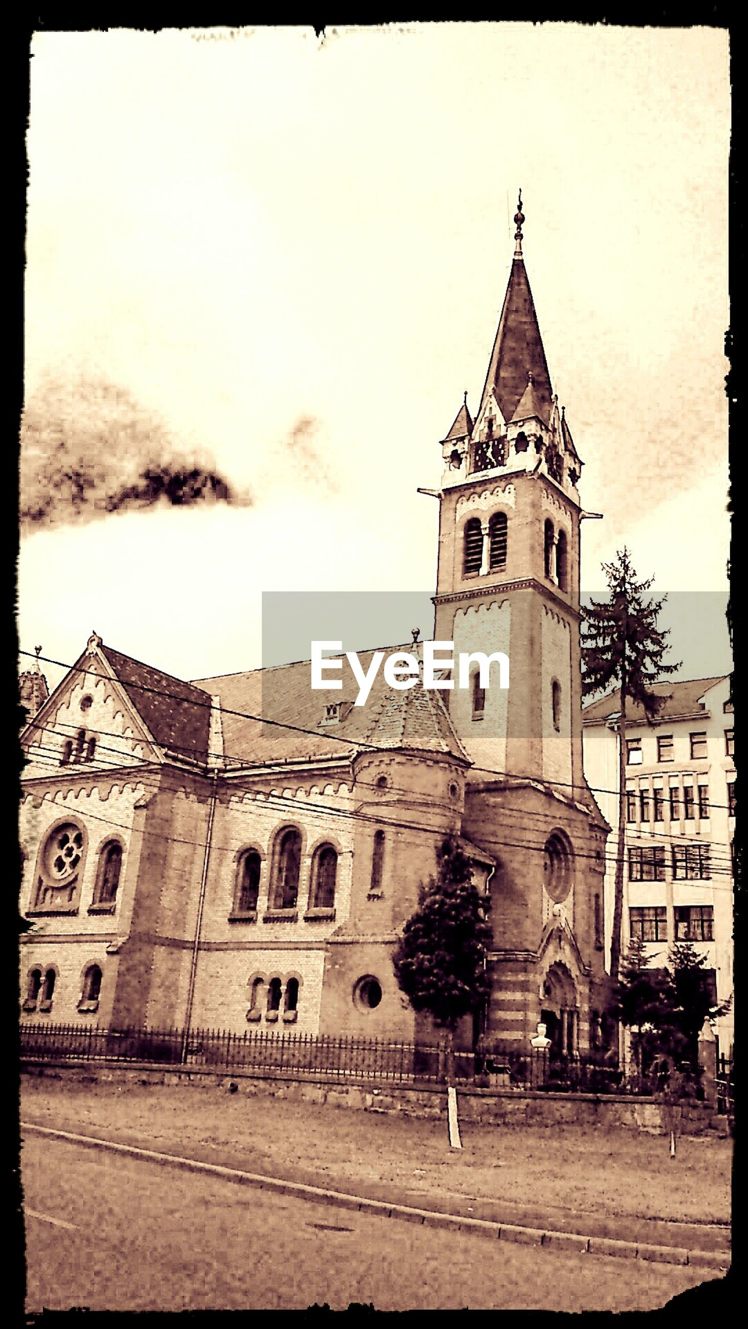 building exterior, transfer print, architecture, built structure, religion, church, place of worship, auto post production filter, spirituality, sky, cathedral, facade, low angle view, history, cross, outdoors, clock tower, day