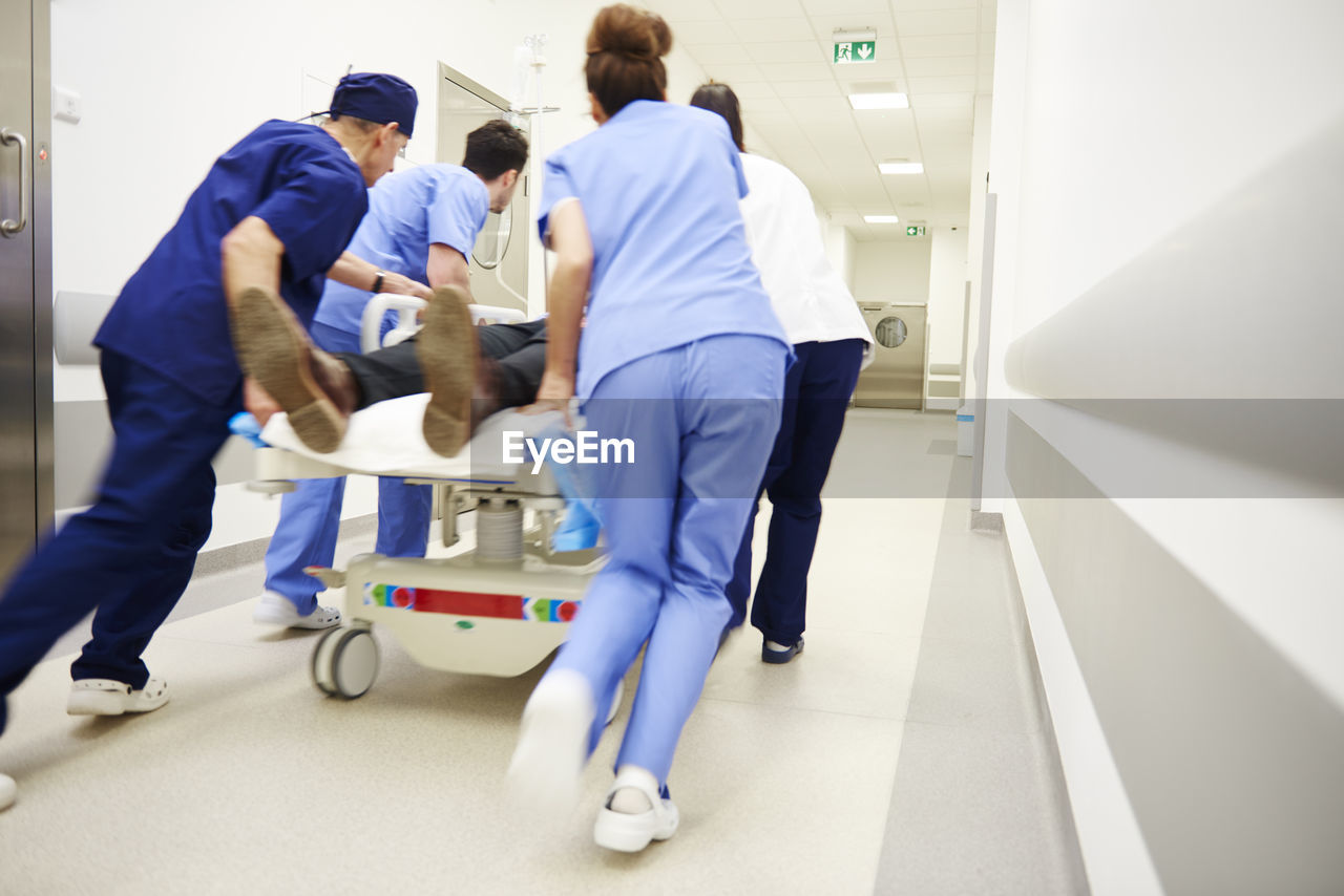 hospital, doctor, healthcare and medicine, occupation, group of people, healthcare worker, nurse, teamwork, men, indoors, architecture, cooperation, corridor, adult, expertise, care, responsibility, arcade, medical clinic, accidents and disasters, coworker, scrubs, mature men, surgeon