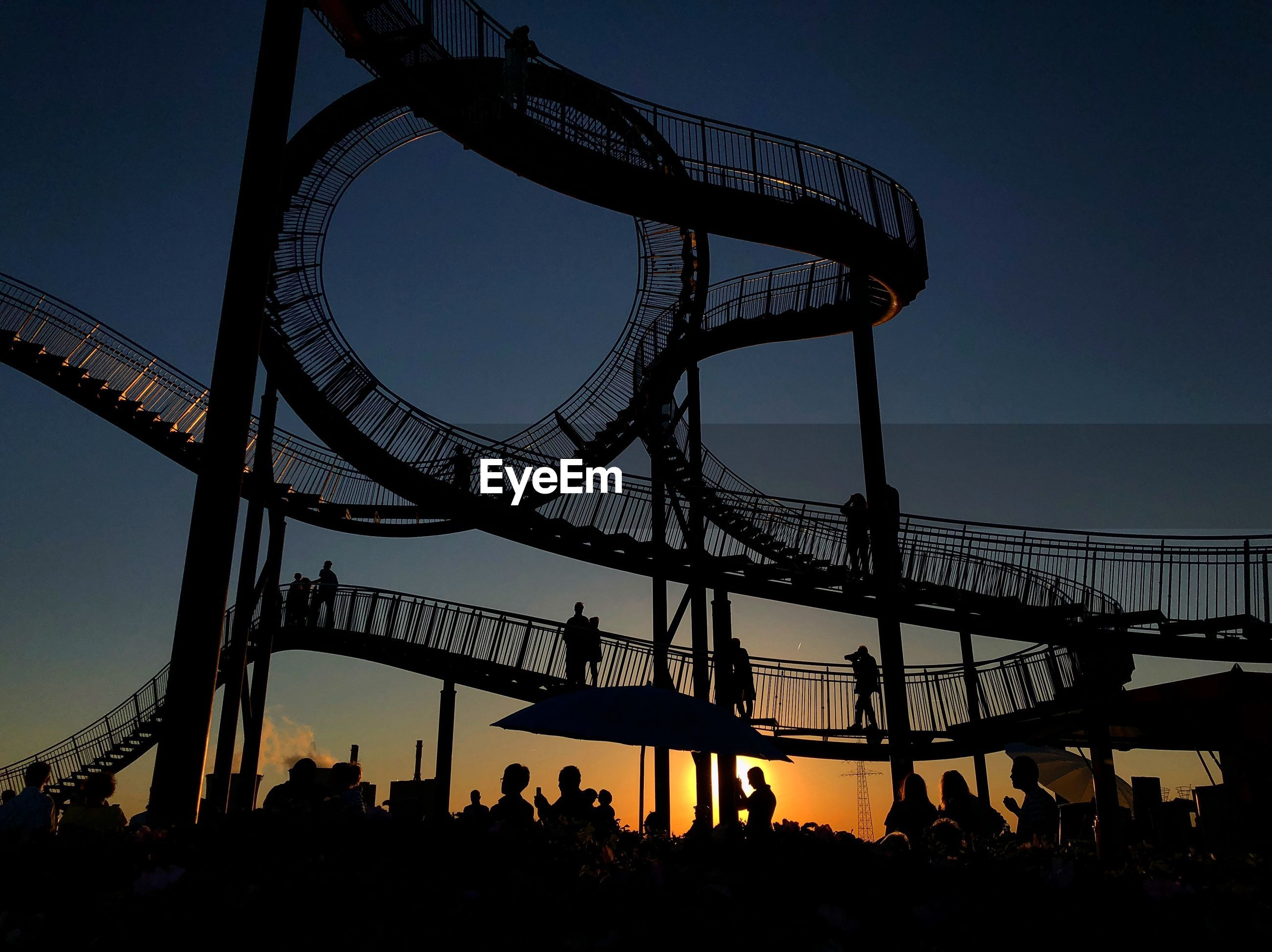 Silhouette people at amusement park against sky during sunset