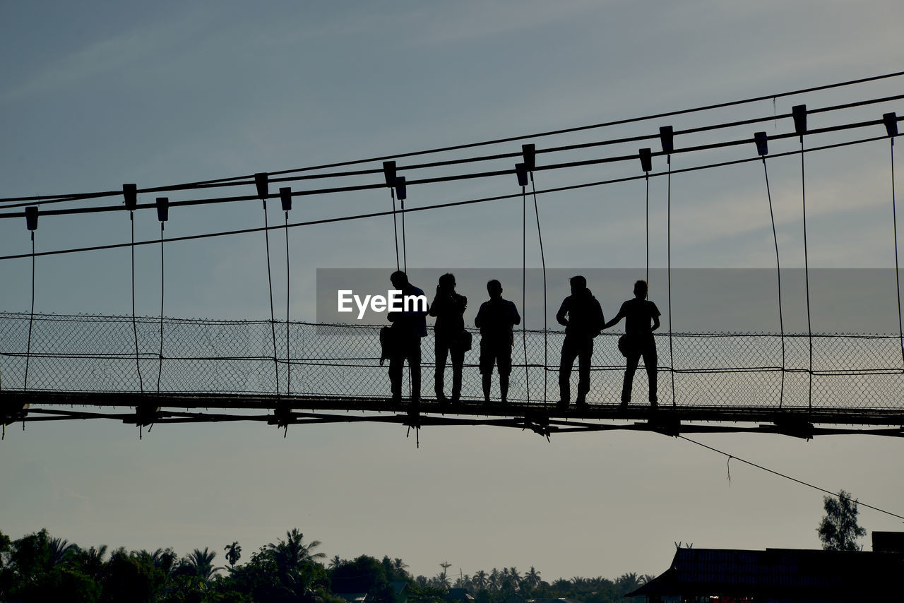 group of people, real people, sky, men, nature, medium group of people, lifestyles, silhouette, architecture, built structure, leisure activity, people, group, connection, outdoors, bridge, standing, rear view, togetherness, full length