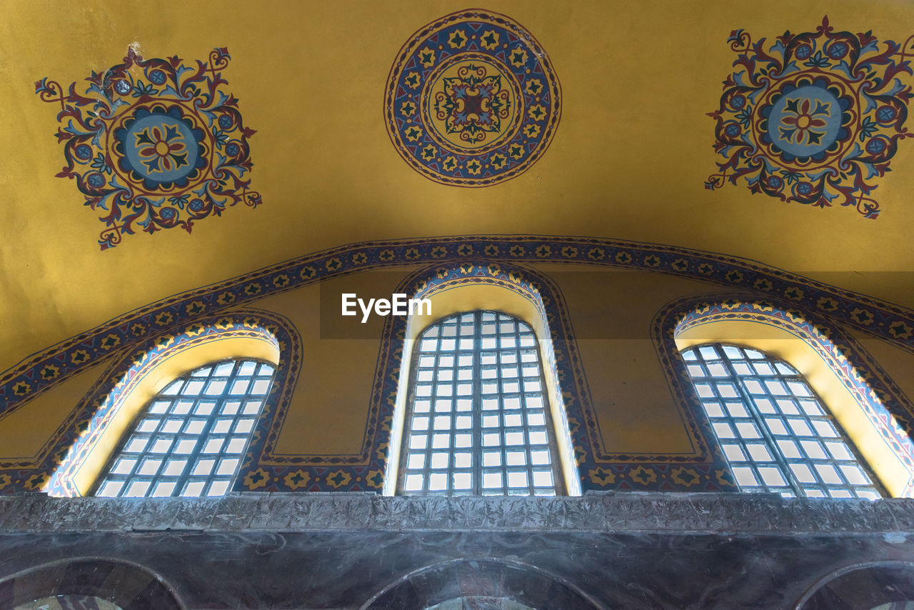 architecture, built structure, indoors, pattern, low angle view, arch, no people, window, building, ceiling, place of worship, art and craft, religion, design, creativity, floral pattern, belief, ornate, day, spirituality, architecture and art, glass