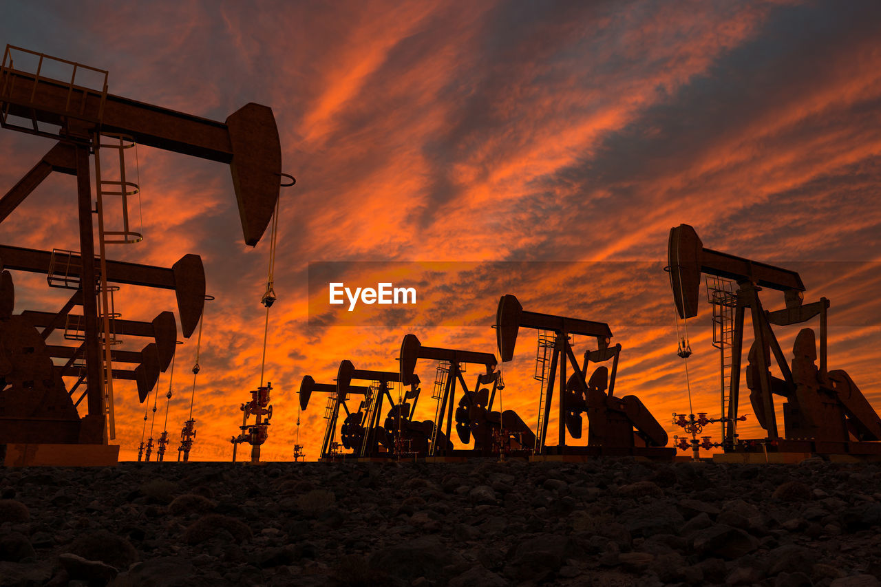 Silhouette Oil Pumps On Field Against Cloudy Sky During Sunset