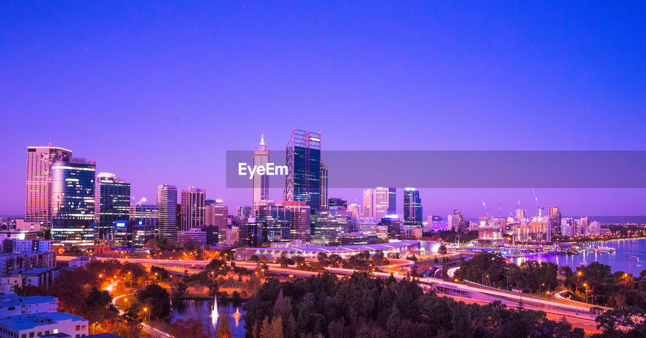 building exterior, architecture, built structure, city, building, office building exterior, urban skyline, illuminated, cityscape, skyscraper, sky, nature, clear sky, night, tall - high, landscape, modern, tower, no people, copy space, outdoors, financial district, purple