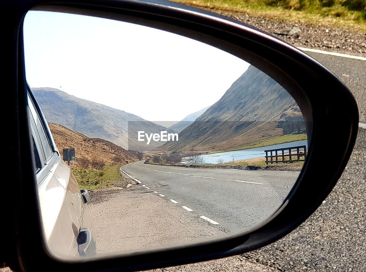 transportation, road, mode of transportation, car, land vehicle, motor vehicle, mountain, side-view mirror, glass - material, vehicle interior, day, transparent, nature, sky, mirror, no people, symbol, window, reflection, mountain range, vehicle mirror, outdoors, road trip