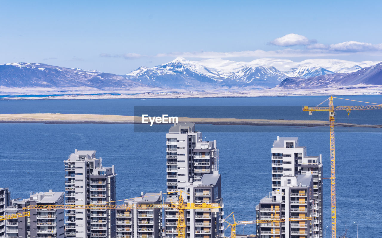 High Angle View Buildings By River Against Snowcapped Mountains