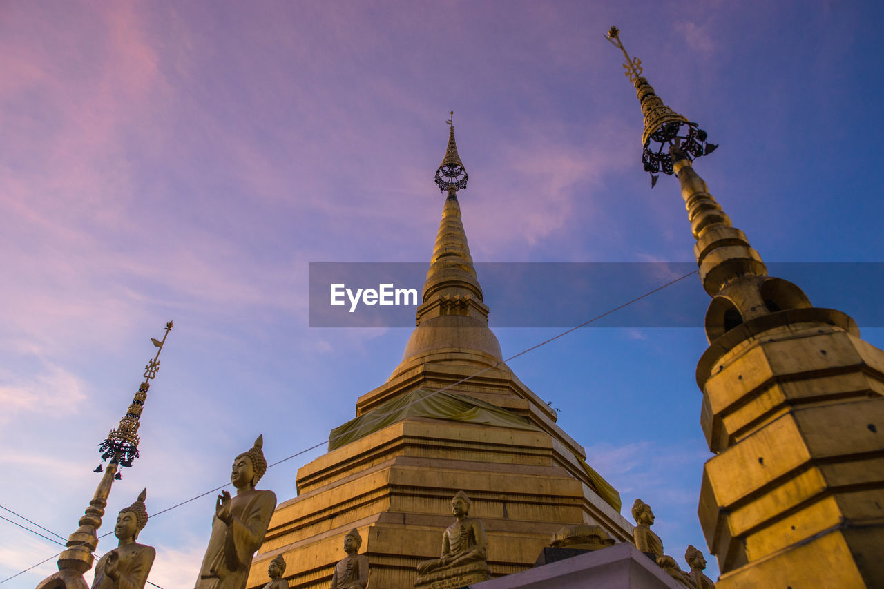 architecture, low angle view, religion, spirituality, statue, travel destinations, built structure, building exterior, place of worship, gold colored, sky, sculpture, history, outdoors, travel, no people, ancient, day