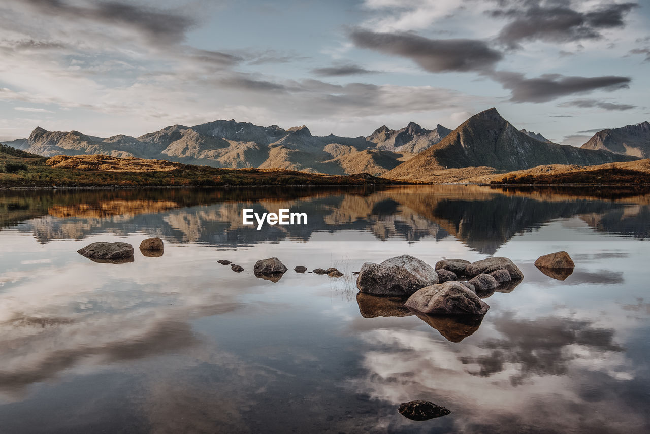 cloud - sky, scenics - nature, water, tranquil scene, mountain, sky, beauty in nature, tranquility, lake, mountain range, reflection, rock, non-urban scene, idyllic, rock - object, nature, solid, no people, environment, outdoors, snowcapped mountain