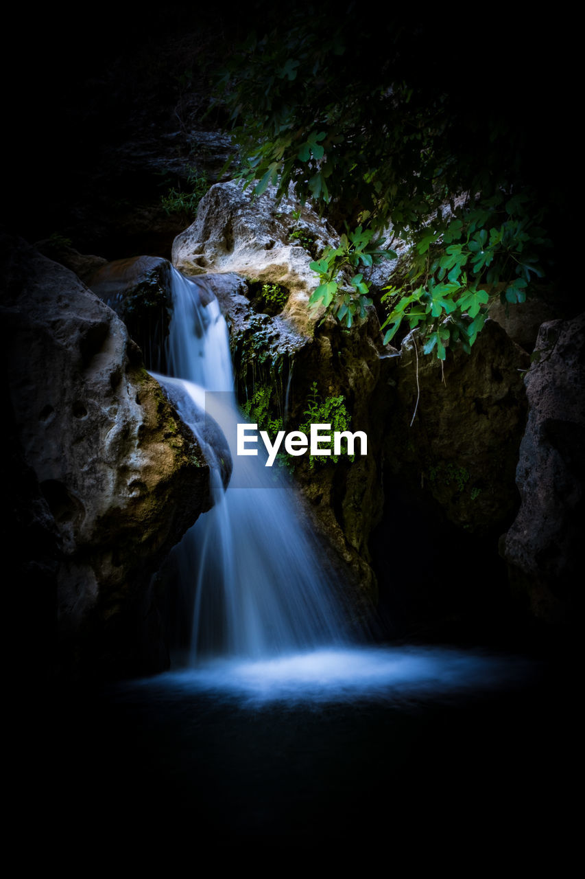 long exposure, waterfall, beauty in nature, motion, rock, scenics - nature, rock - object, water, solid, blurred motion, flowing water, rock formation, no people, forest, land, nature, flowing, tree, non-urban scene, outdoors, power in nature, falling water, black background