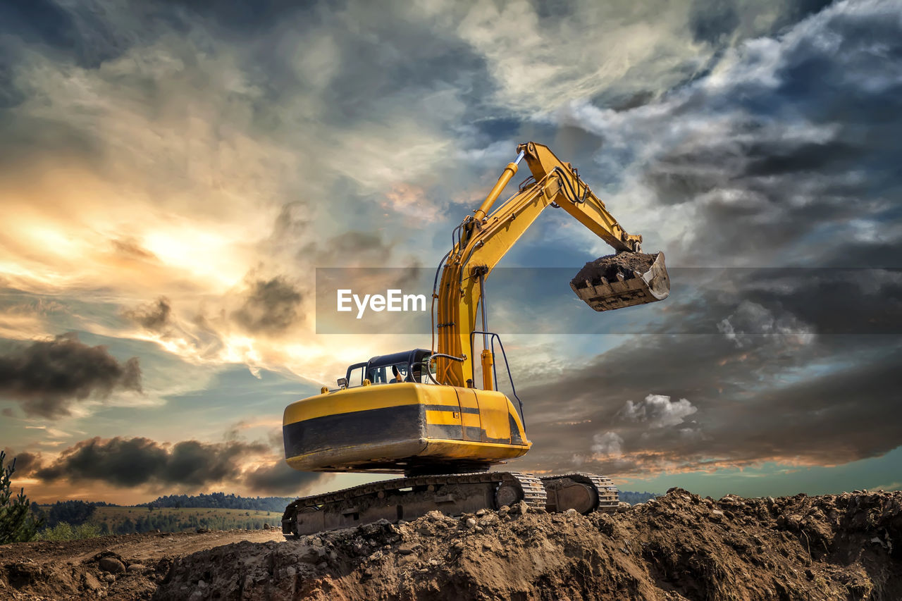 cloud - sky, sky, construction machinery, machinery, earth mover, construction industry, bulldozer, construction site, nature, industry, transportation, sunset, yellow, construction vehicle, mode of transportation, digging, land, no people, road, development, construction equipment, industrial equipment