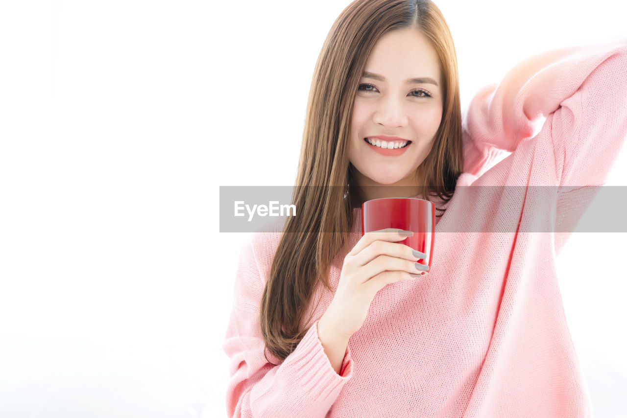 Portrait Of Smiling Woman Having Coffee Against White Background