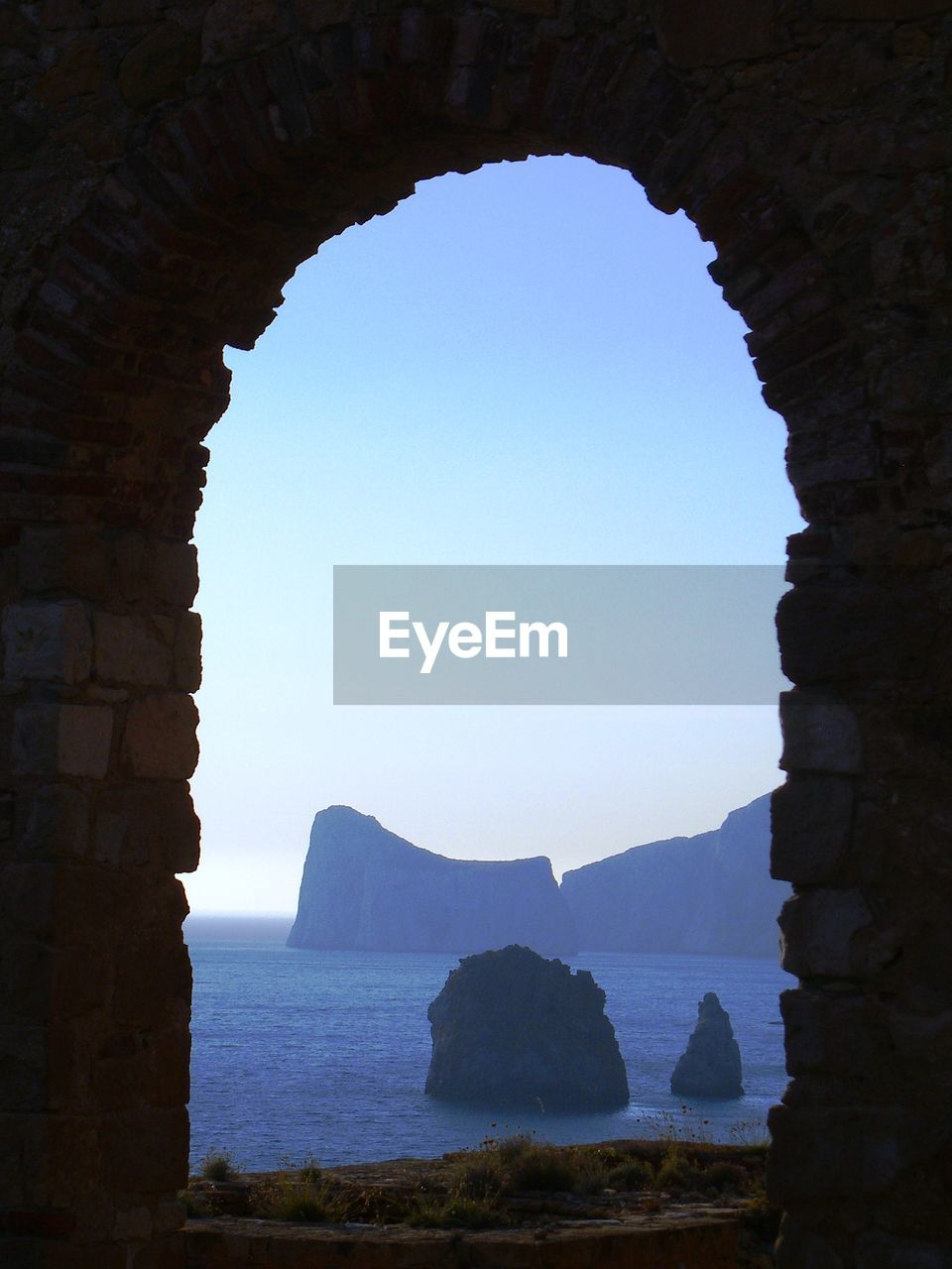 Scenic view of rock formations in sea seen through window