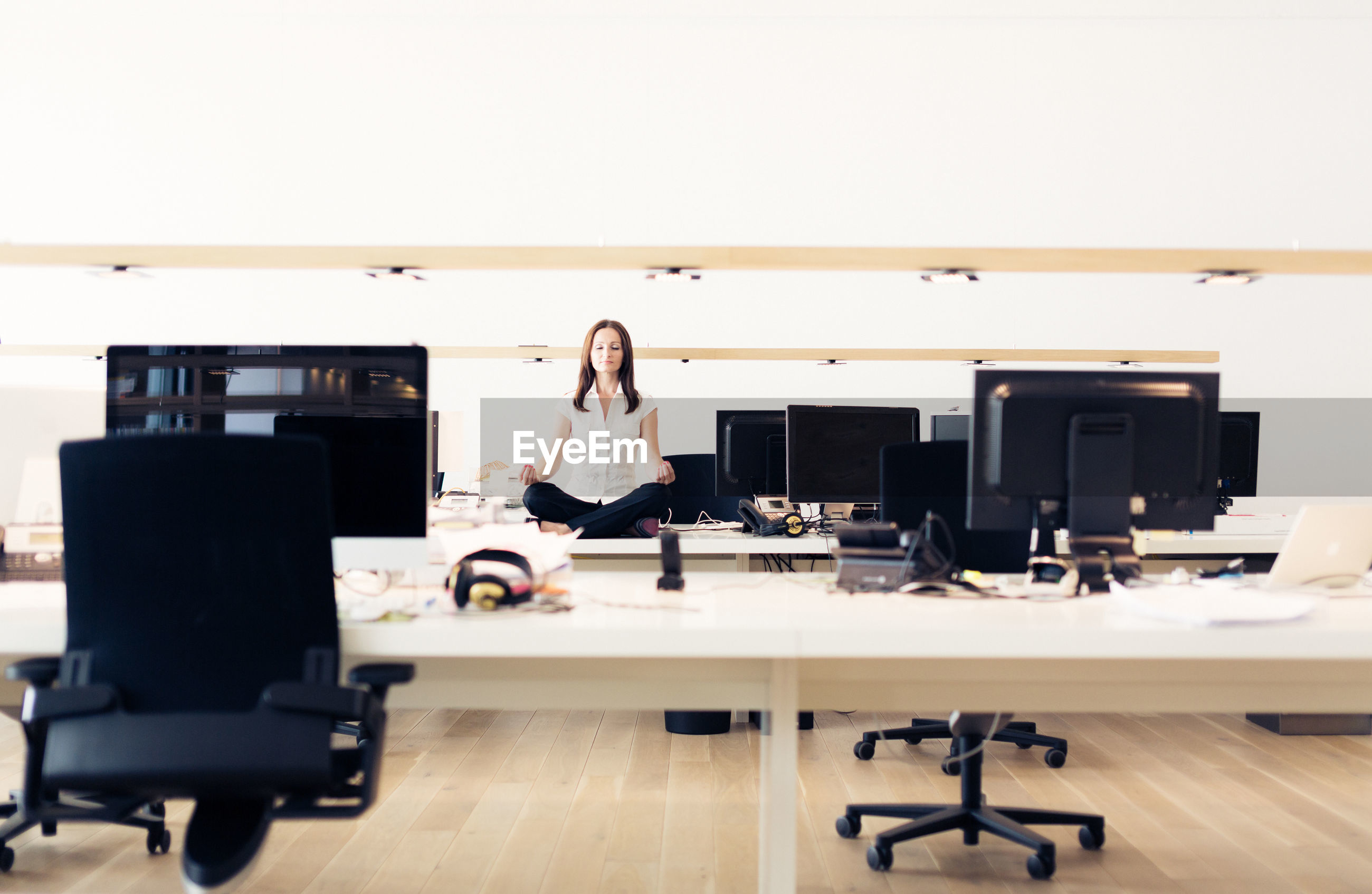 Woman meditating on table in office
