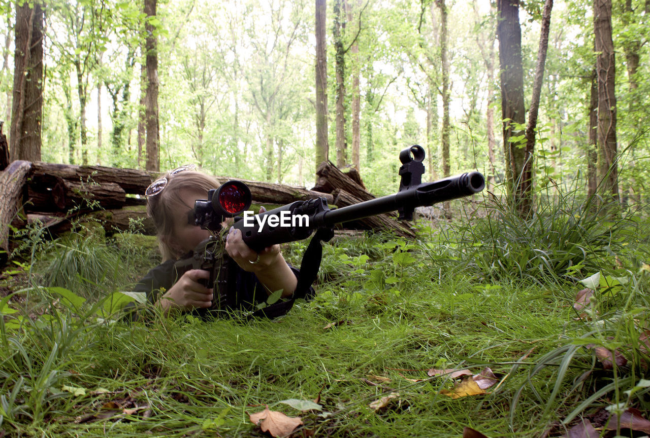 Woman Aiming With Sniper At Forest