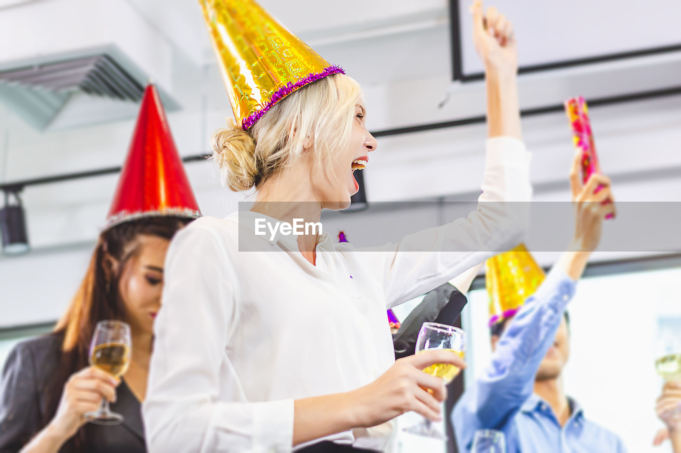 Cheerful colleagues wearing party hat celebrating in office