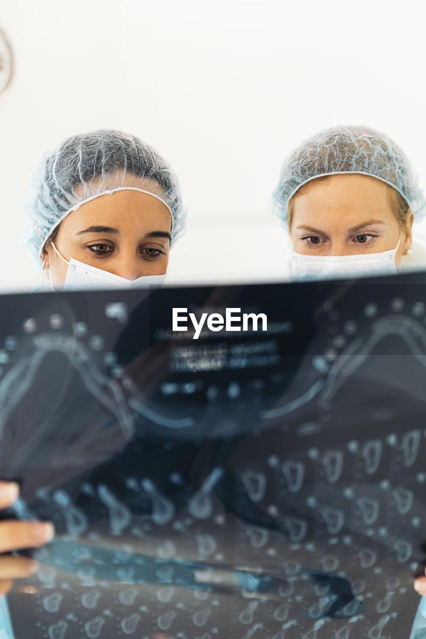 Female dentists examining x-ray at clinic