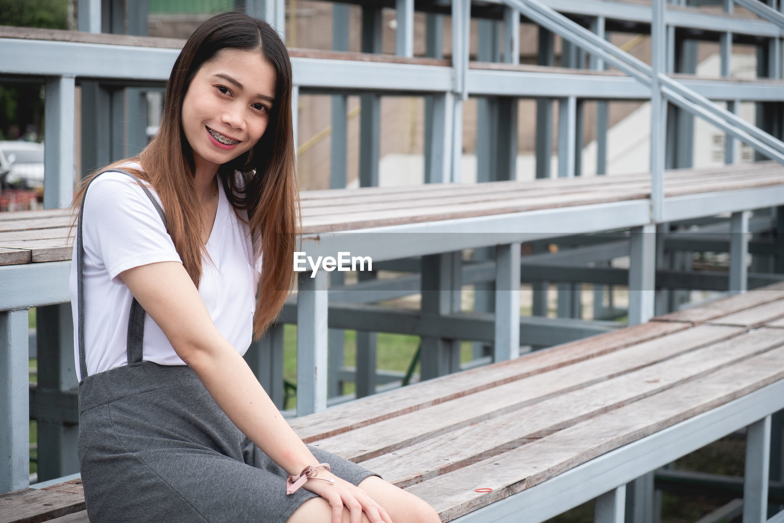 Portrait of young woman smiling while standing at stadium