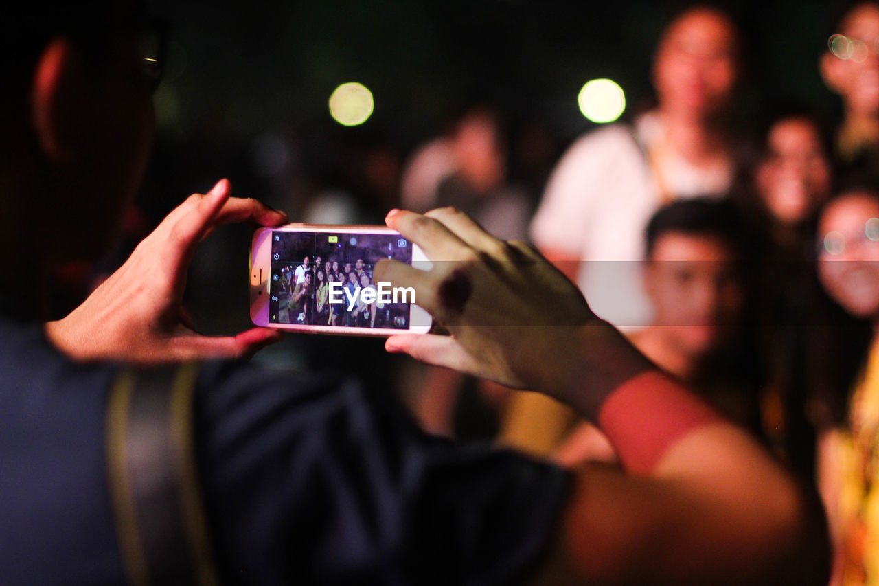 wireless technology, real people, technology, smart phone, communication, group of people, photography themes, photographing, portable information device, lifestyles, mobile phone, holding, enjoyment, women, togetherness, activity, leisure activity, adult, crowd, focus on foreground, nightlife