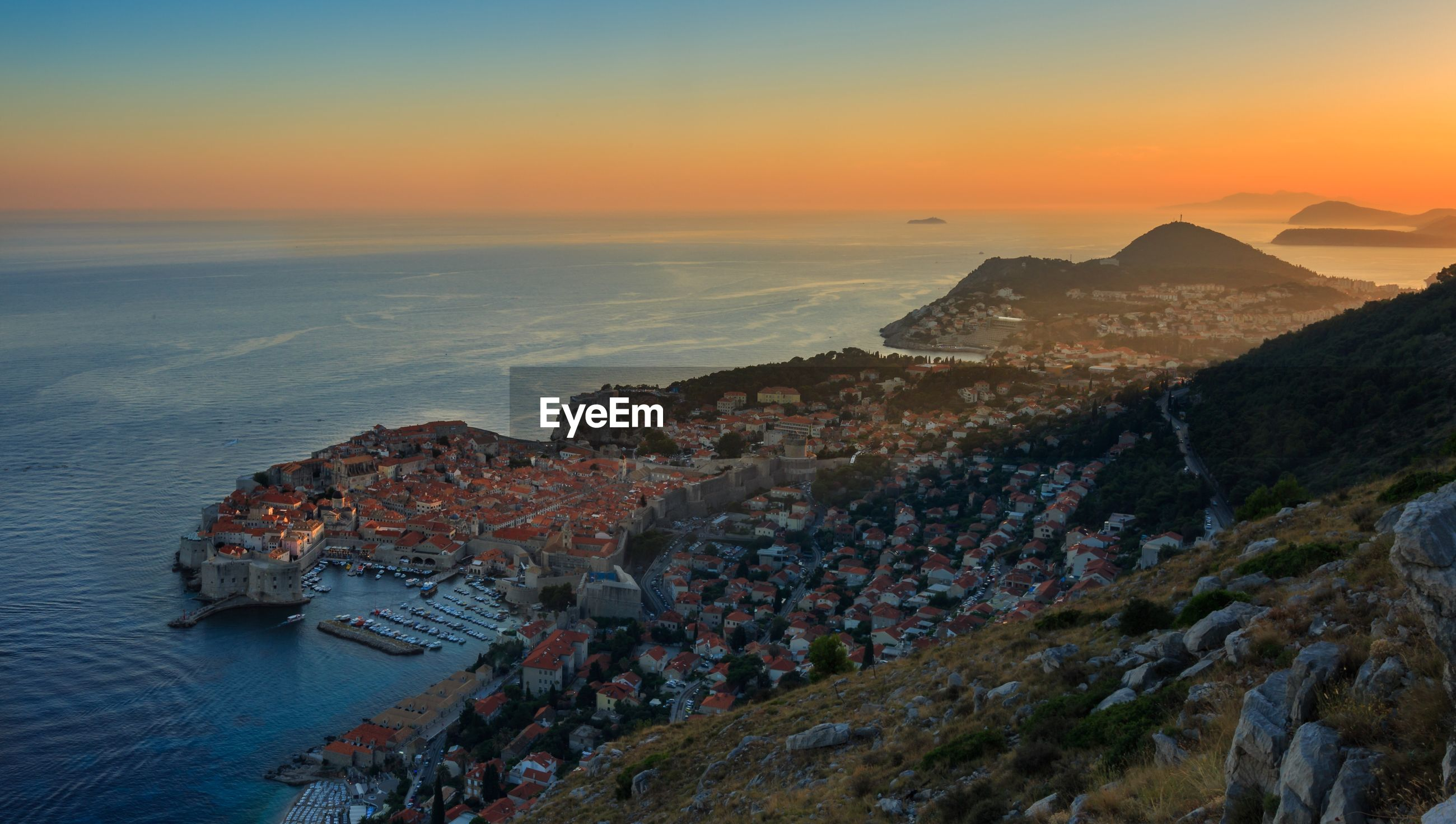 HIGH ANGLE VIEW OF TOWN BY SEA AT SUNSET