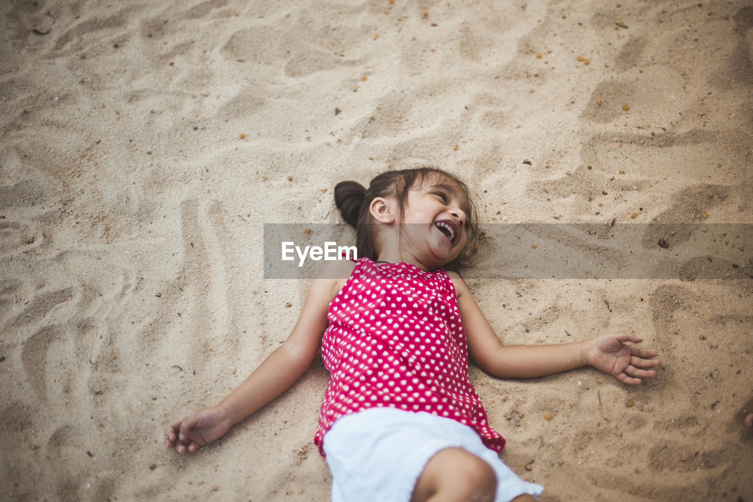 High angle view of girl lying on sand