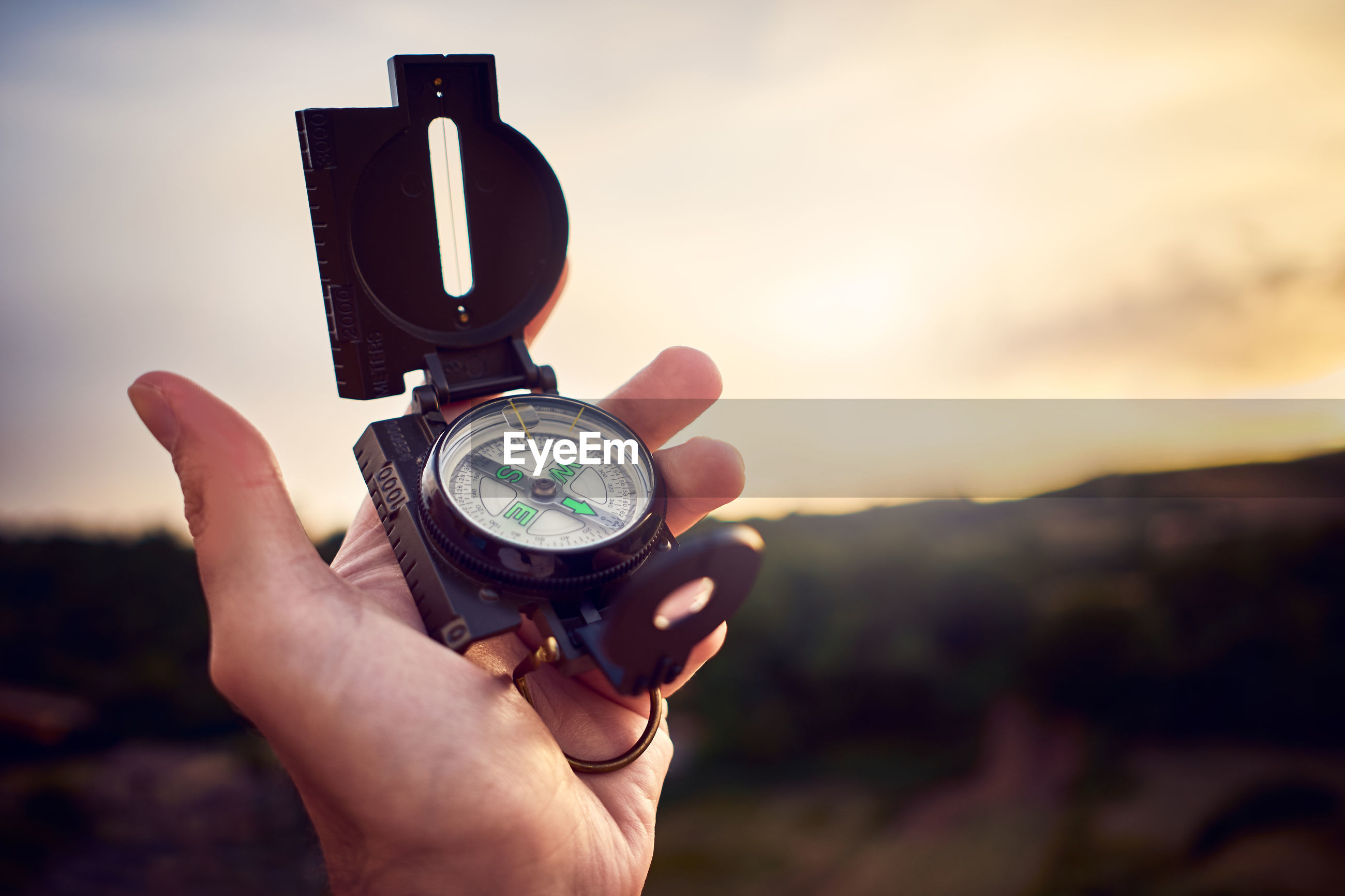 A human hand holds a vintage compass at sunset on hills
