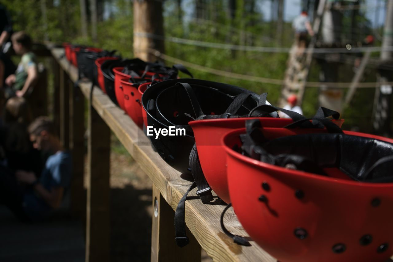 focus on foreground, day, incidental people, red, outdoors, real people, transportation, men, mode of transportation, group, land vehicle, nature, close-up, metal, wood - material, railing, helmet, group of people, people, safety