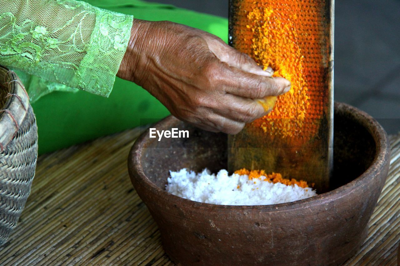 Cropped Image Of Woman Grating Turmeric In Container