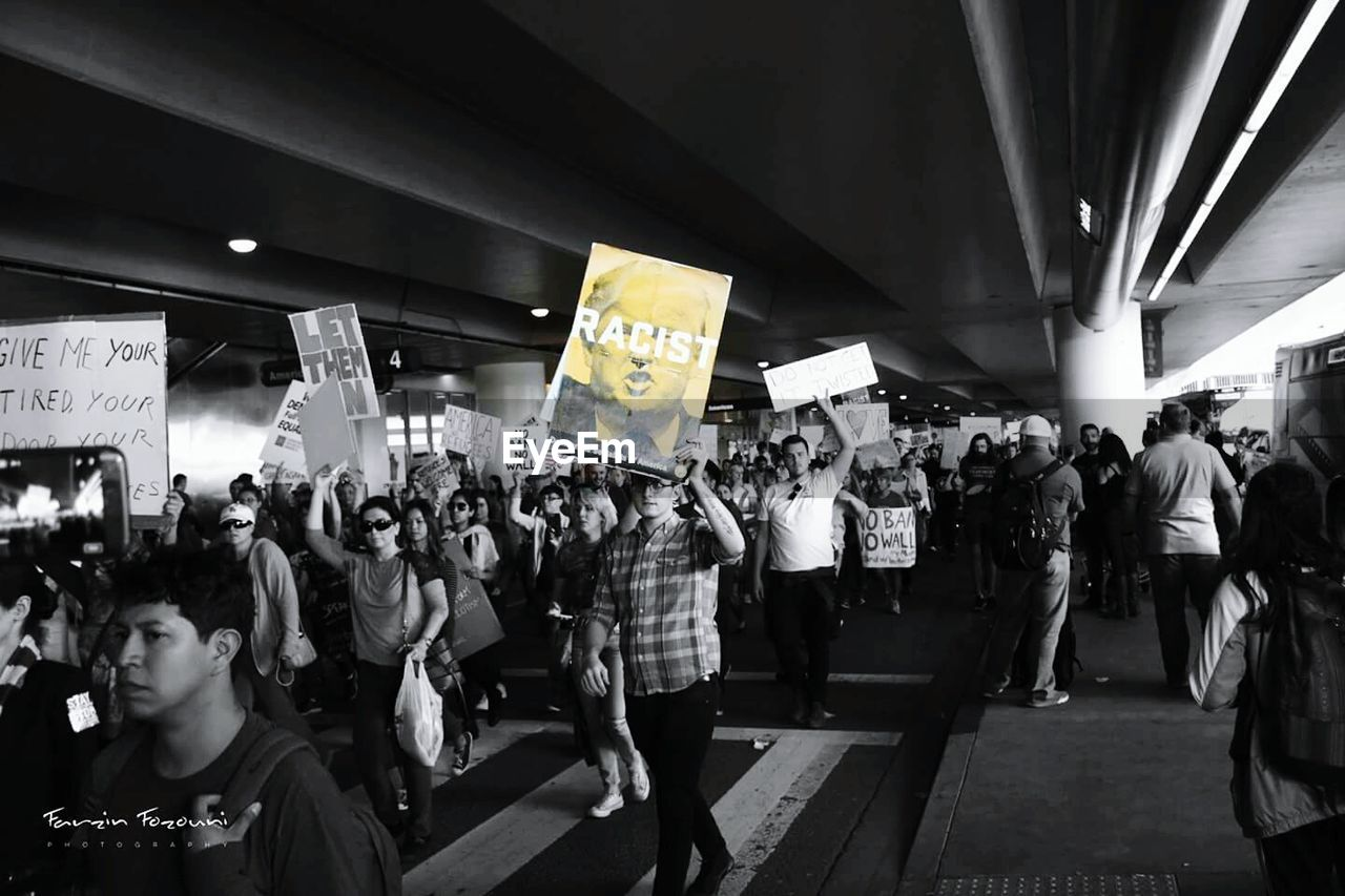 large group of people, real people, placard, men, text, banner - sign, crowd, leisure activity, women, protestor, standing, lifestyles, night, indoors, adult, people