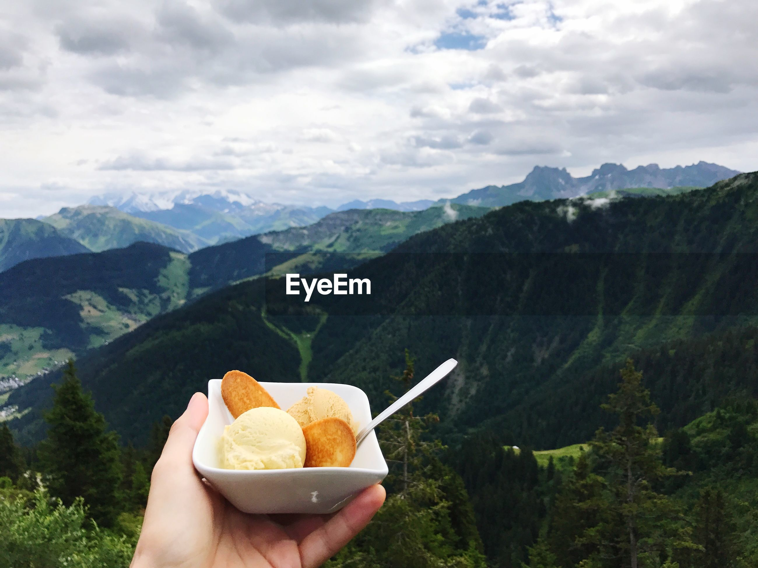 Cropped hand of woman holding ice cream on mountain against cloudy sky