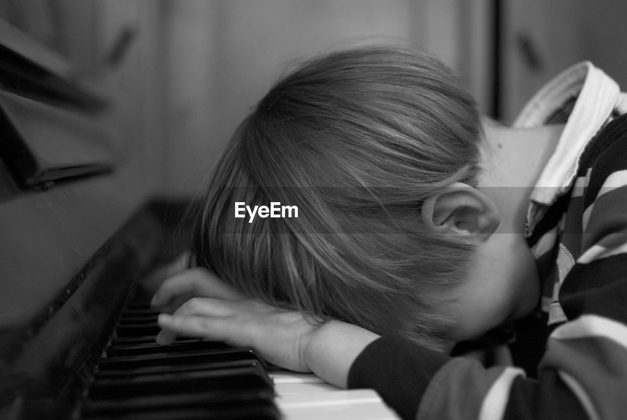 Side View Of Boy Leaning While Playing Piano