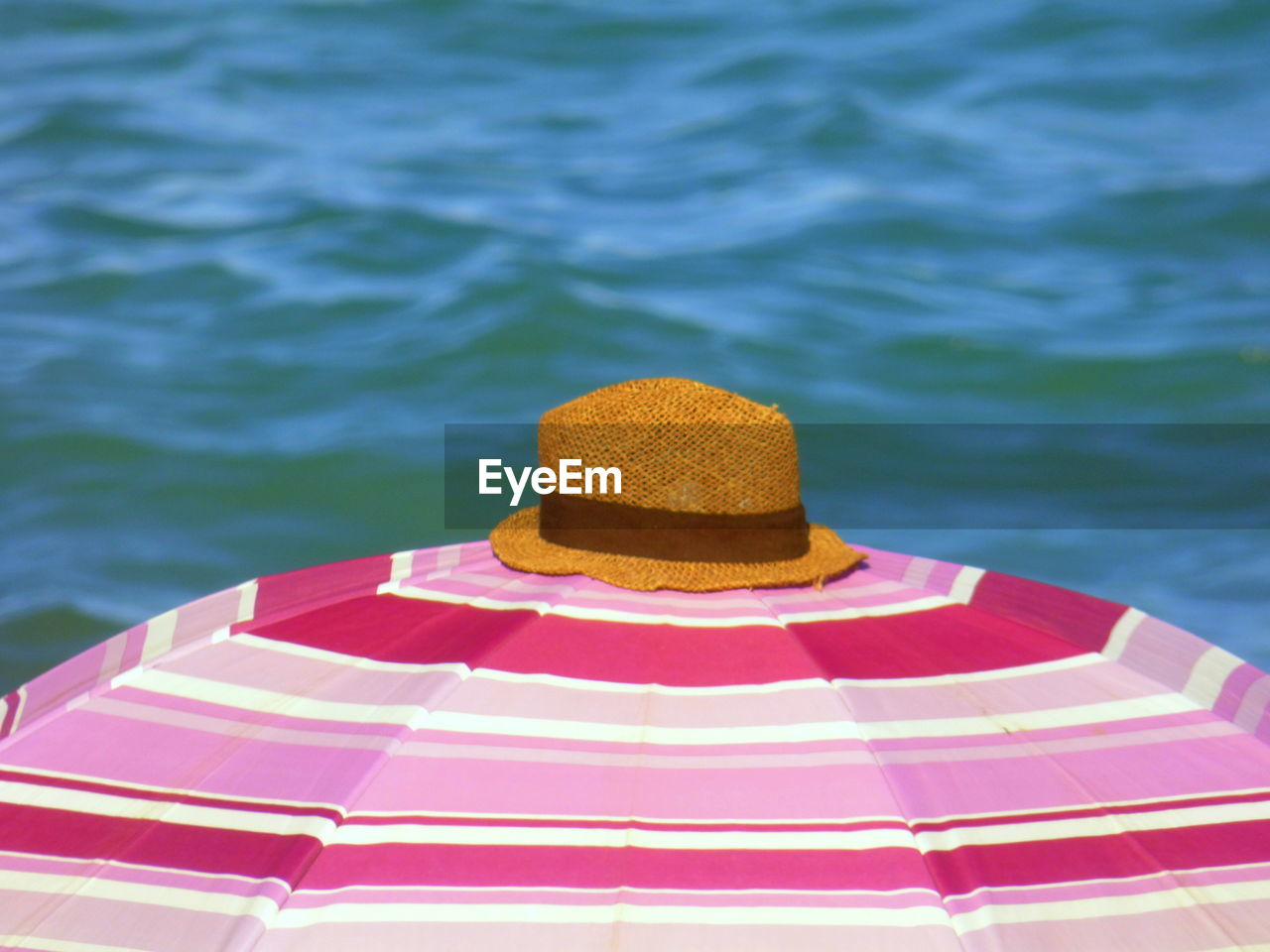 High Angle View Of Sun Hat On Open Pink Parasol Against Sea